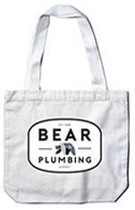 light grey tote bag on a white background with bear plumbing branding
