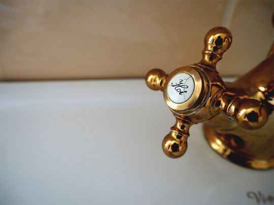 closeup of hot water bronze tap in the bathroom.